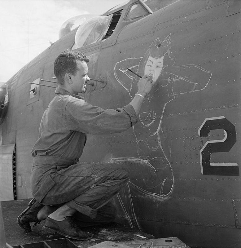 Homem pintando uma pin-up em uma aeronave, em 1944.