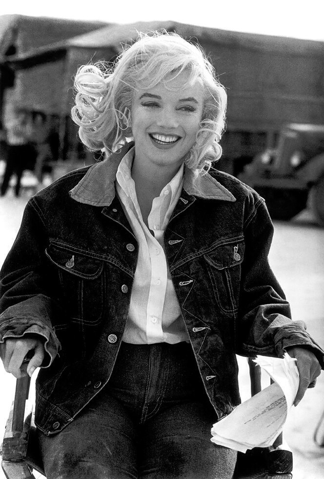 Foto em preto e branco de Marilyn Monroe sentado e sorrindo vestida com jaqueta e calça jeans