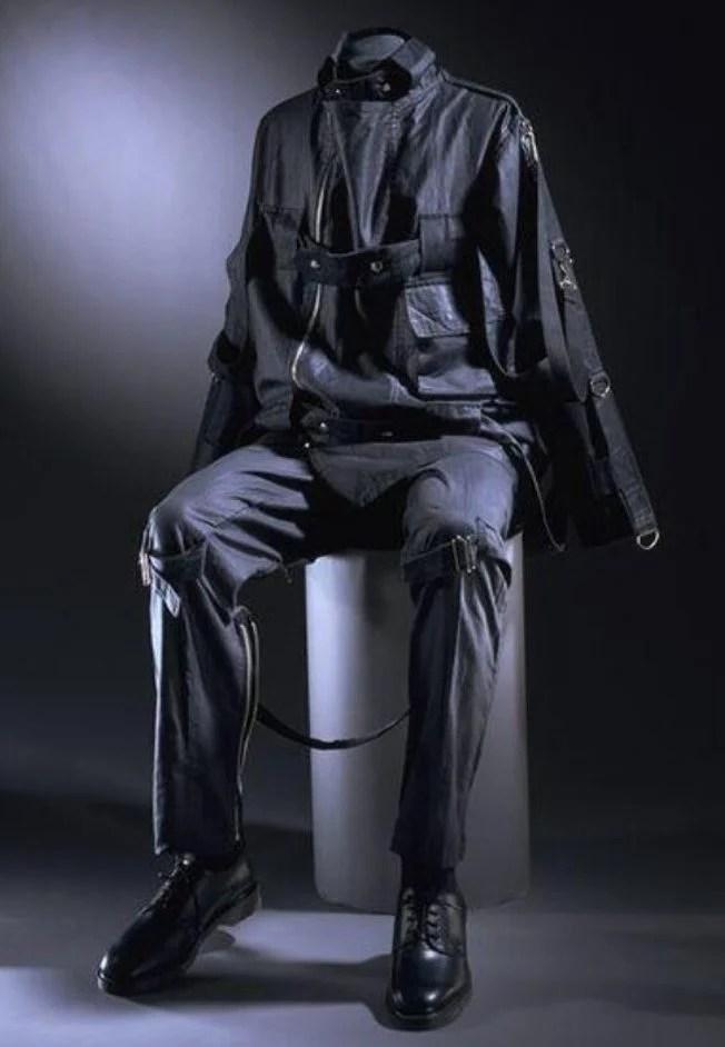 Foto de um manequim sentado vestindo um traje punk formado por jaqueta e calça pretas adornadas com vários modelos de zíper de Vivienne Westwood e Malcolm McLaren em fundo preto