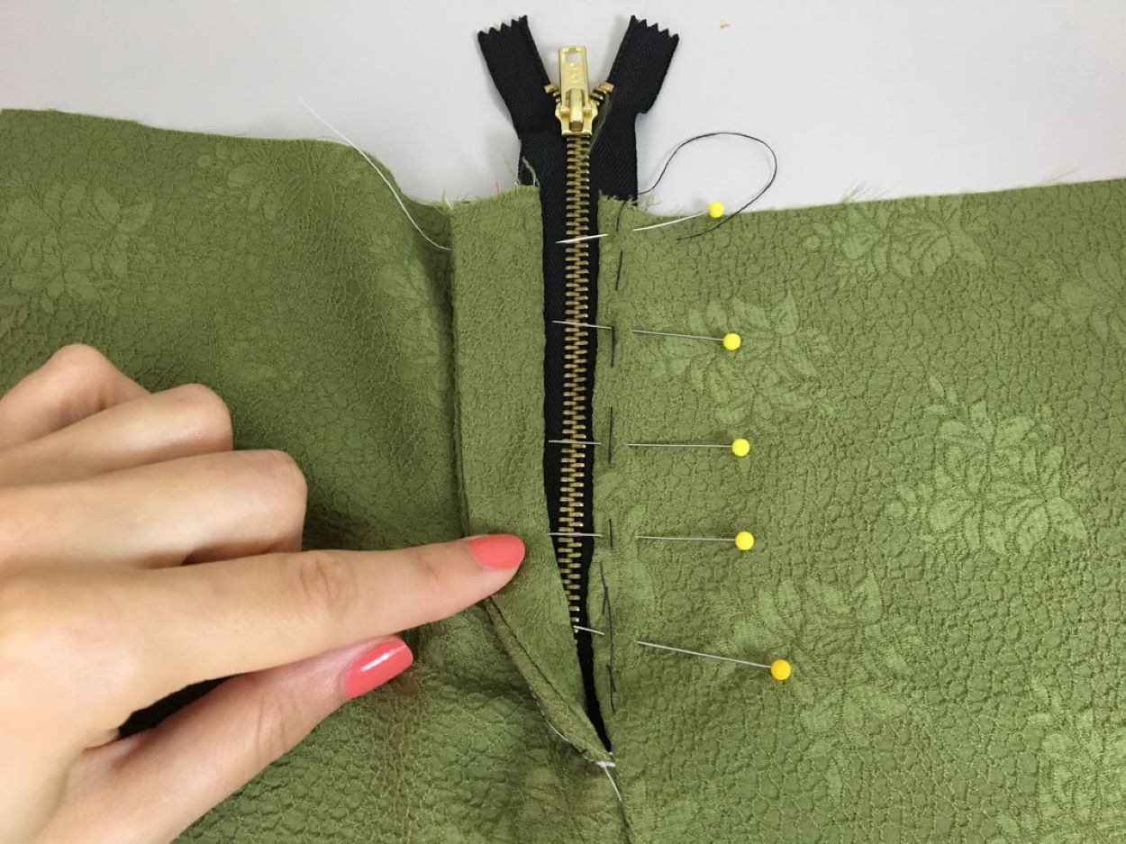 Foto de uma mão de mulher a mostrar o detalhe de uma roupa a ser costurada com um zíper