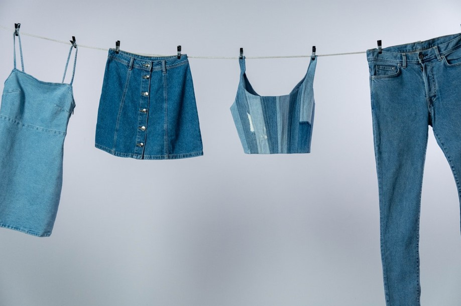 Foto de diferentes roupas jeans estendidas em um varal com fundo branco