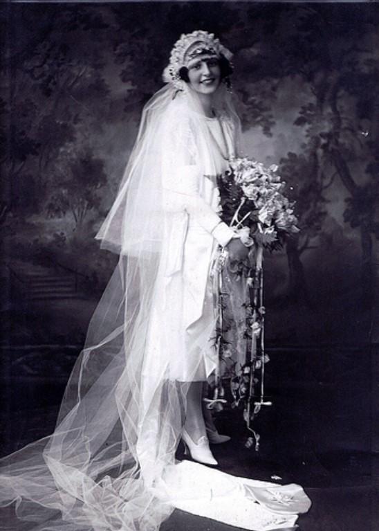 Peggy Fish posando nos anos 20 com um vestido de noiva branco de cetim, véu e buquê de flores.