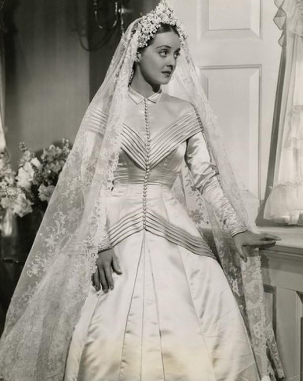 Bette Davis em um vestido de noiva branco acetinado e um véu transparente.