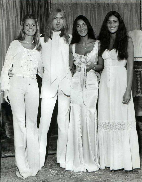 Cher ao lado do seu marido e amigas no seu casamento nos anos 70 com um vestido de noiva branco acetinado e ajustado.