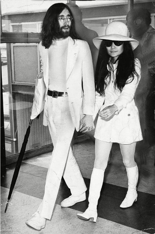 Yoko Ono com um vestido de noiva branco curto e John Lennon no dia do seu casamento, em 1969.