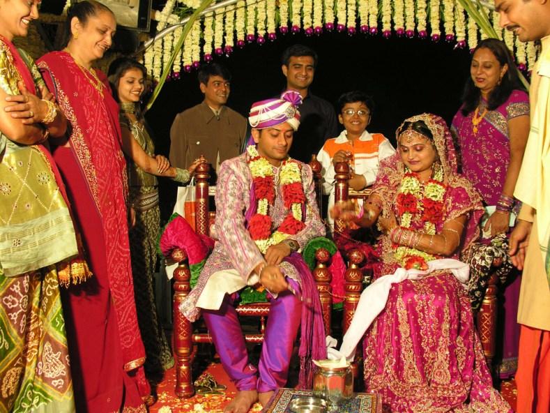 Foto de um casamento hindu com os noivos ao centro vestindo roupas muito coloridas e ricamente ornamentadas.