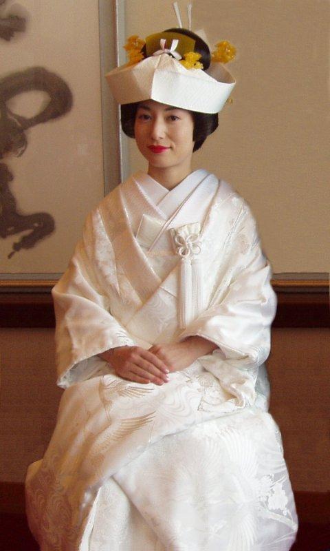 Mulher japonesa sentada com um quimono de casamento branco e chapéu.
