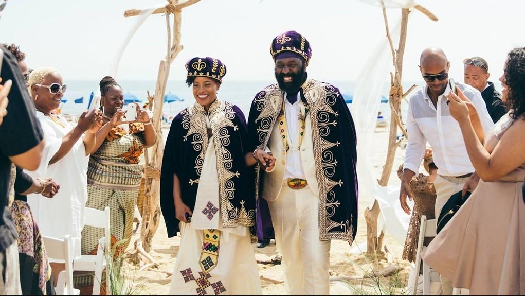 Casal em uma cerimônia ao ar livre com traje de casamento tradicional da Eritreia.