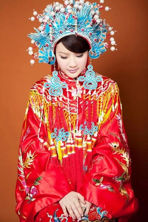 Foto de uma mulher com um vestido de noiva tradicional chinês vermelho e coroa ornamentada azul.