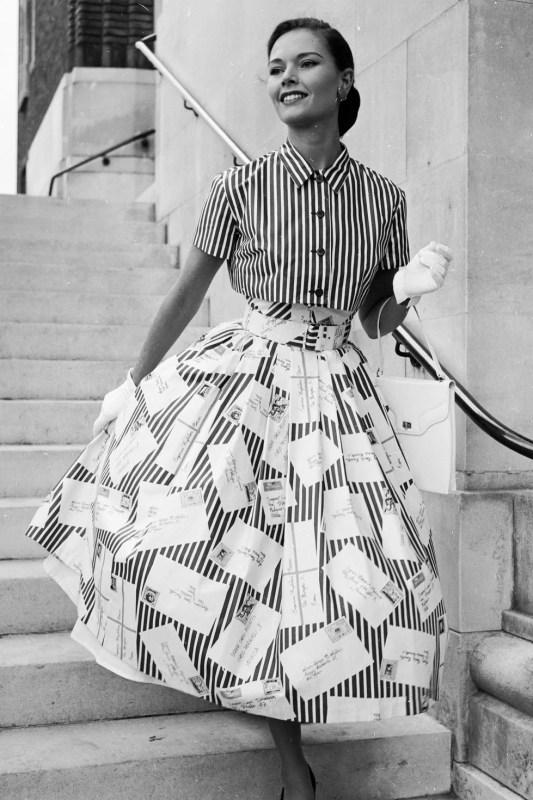 Modelo a posar com uma saia e camisa listradas nos anos 50, com luvas brancas nas mãos.