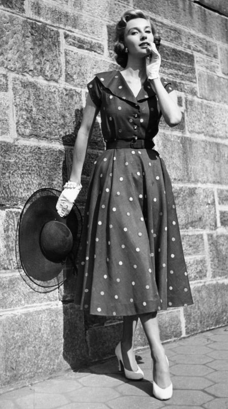 Uma modelo posando com um vestido de verão dos anos 50, com luvas brancas e chapéu preto nas mãos. A Moda e Cidadania nos anos 40 e 50.
