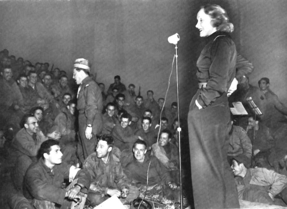 A atriz Marlene Dietrich a entreter soldados do exército, em 1944, vestida com calça e camisa. A Moda e Cidadania nos anos 40 e 50.