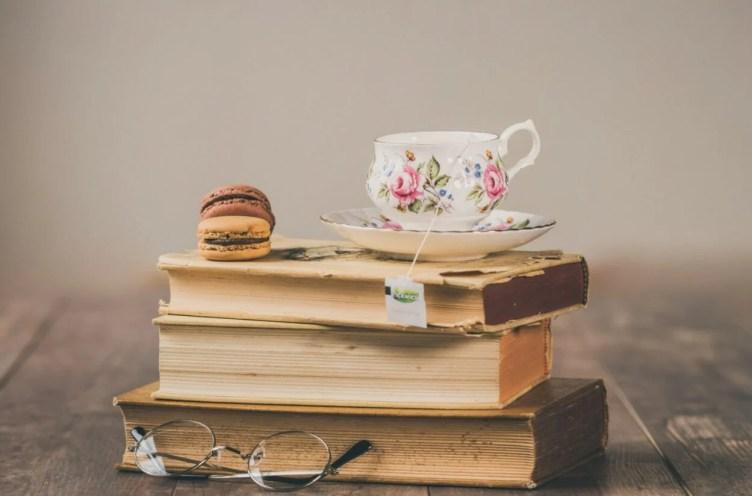 livros e um docinho e um óculos e uma xícara de chá