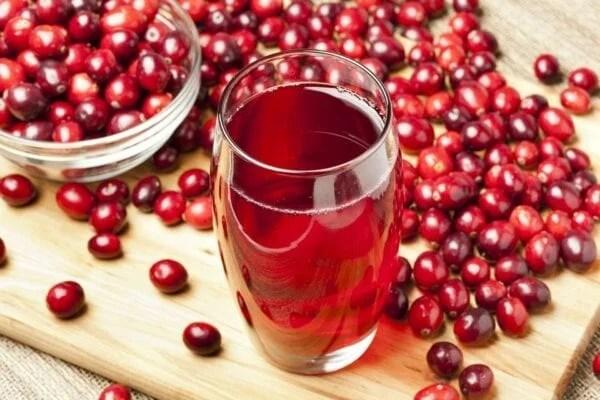 Foto de frutos Cranberry e copo de suco da fruta