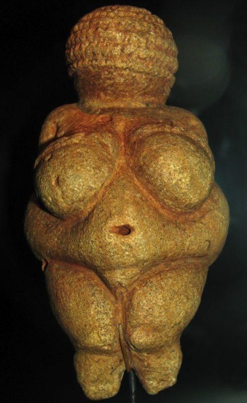 Foto da estátua Vênus de Willendorf em um fundo preto