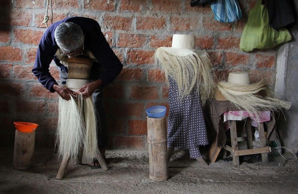 Artesão agachado a trabalhar a confeccionar um Chapéu-Panamá