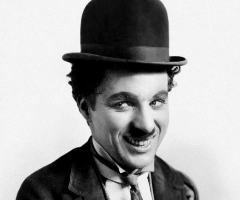 Charles Chaplin como Carlitos com bigode e chapéu coco