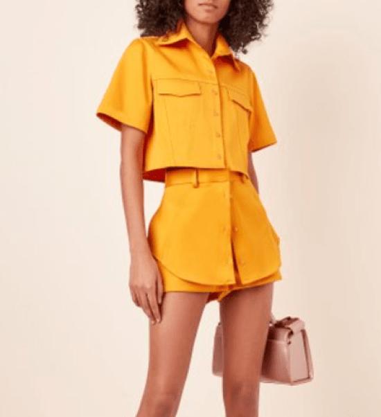 Conjunto monocromático amarelo com camisa manga curta e short saia com botões.