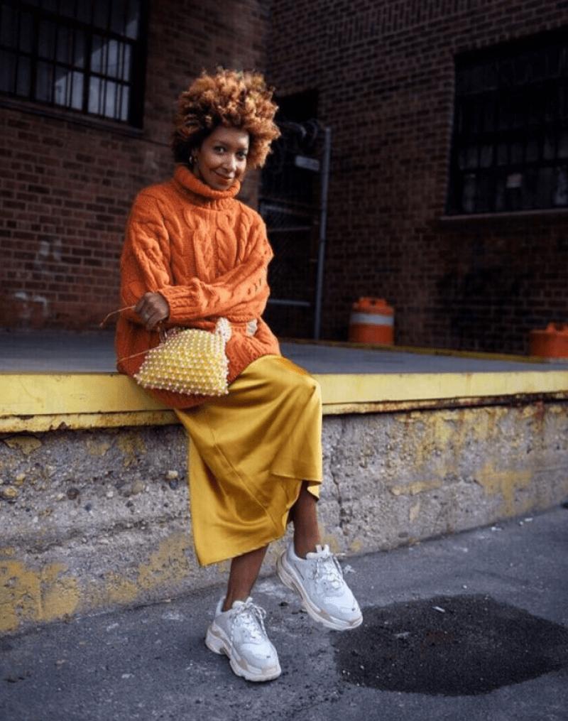 Tricô com saia midi acetinada e tênis esportivo