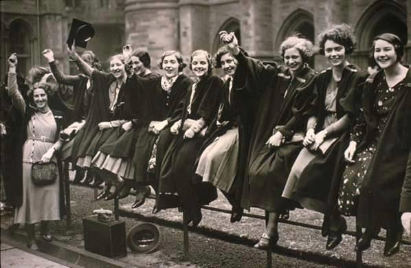 mulheres em foto preto e branco sentadas em grade comemorando