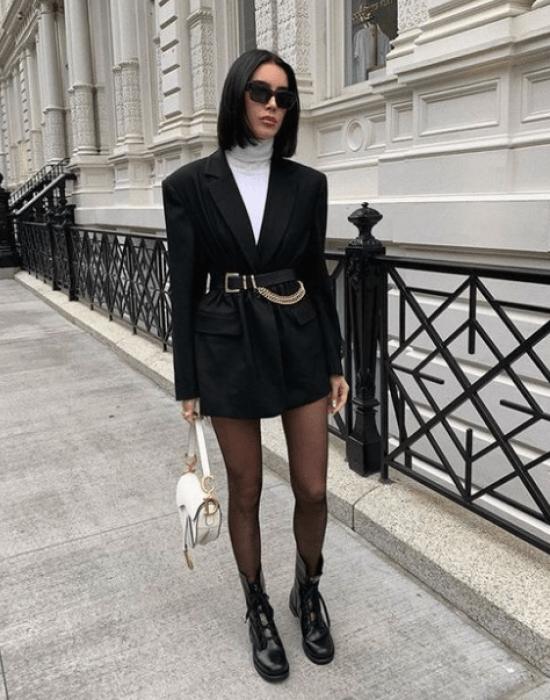 Mulher usa blazer com cinto de elos, botas e blusa de gola.