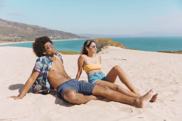 vitamina d homem e mulher tomando sol na areia