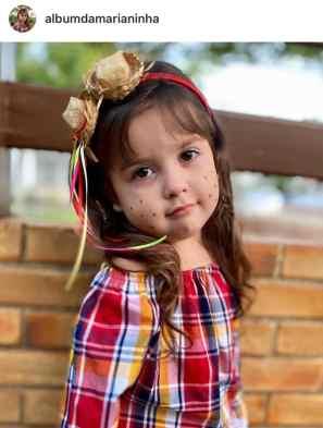 Foto de garotinha com maquiagem de festa Junina com sardas e tiara decorada com fitas e chapéu de palha
