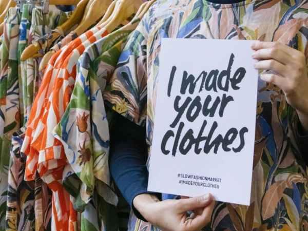 Foto de mulher na frente de arara com roupas penduradas segurando um cartaz com os dizeres: Eu faço suas roupas em inglês