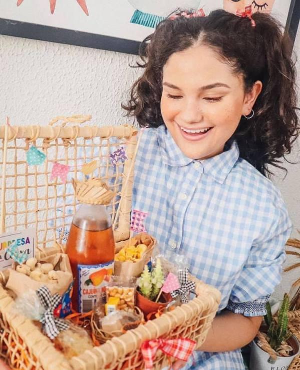 Menina com traje junino segura cesta de festa Junina delivery - Com várias cominhas tradicionais de São João