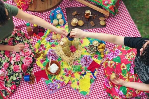 Piquenique de festa junina com toalha xadrez vichy e comidinhas tradicionais de são joão como pamonhas