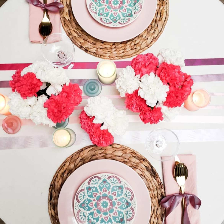 Foto de mesa posta para jantar romêntico decorado com flores vermelhas e brancas