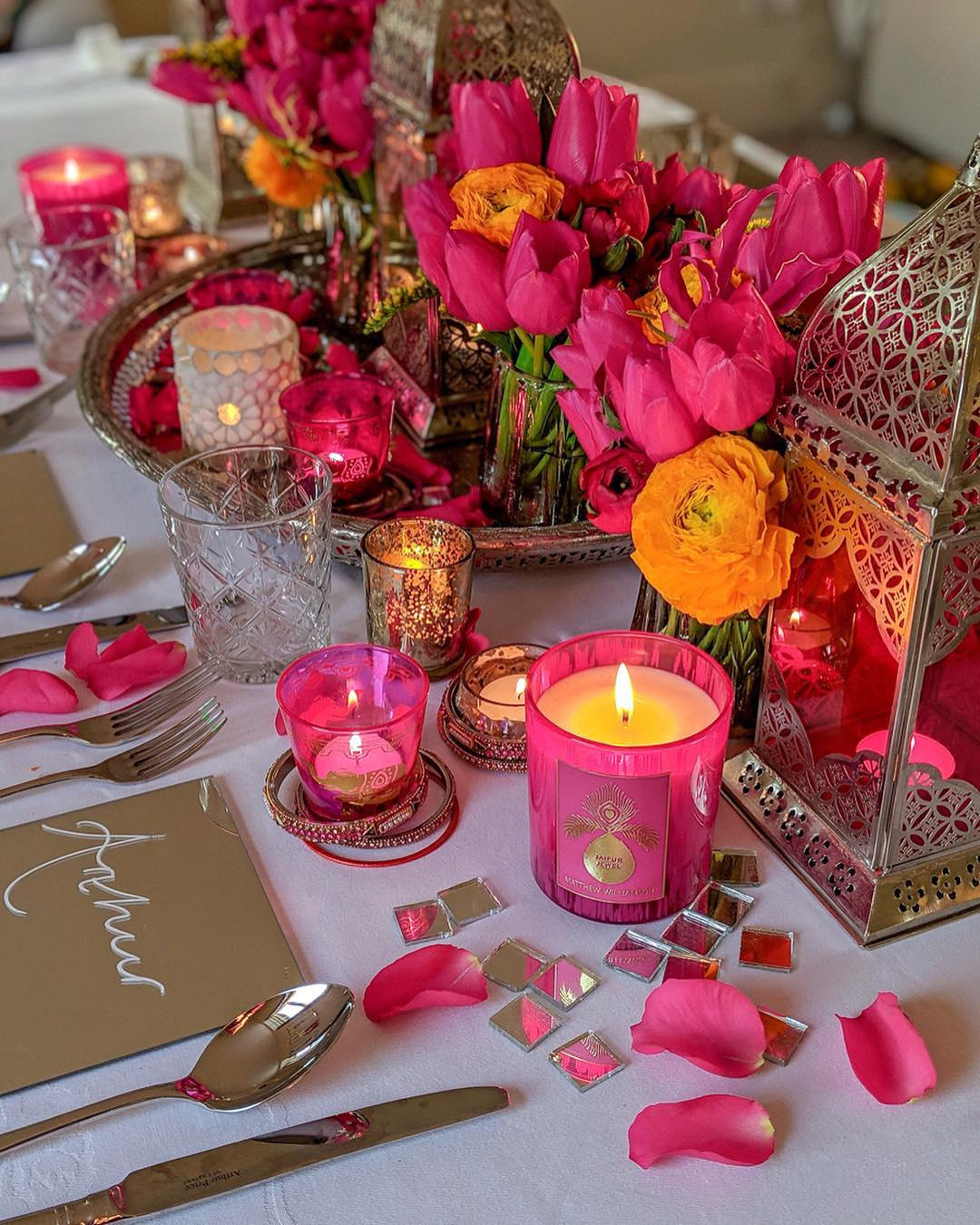 Foto de mesa decorada com rosas, pétalas e velas em tons de pink
