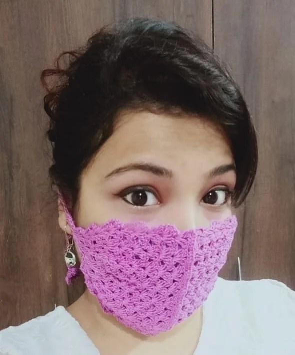 Foto de mulher com Máscara de proteção em crochê pink