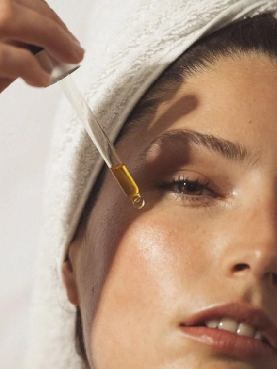 Foto de mulher com conta gostos fazendo aplicação de óleo no rosto