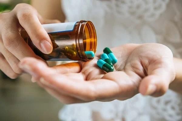 Foto de mãos com vidro de remédio e capsulas de comprimidos na palma das mão nas mãos - Infecção urinária