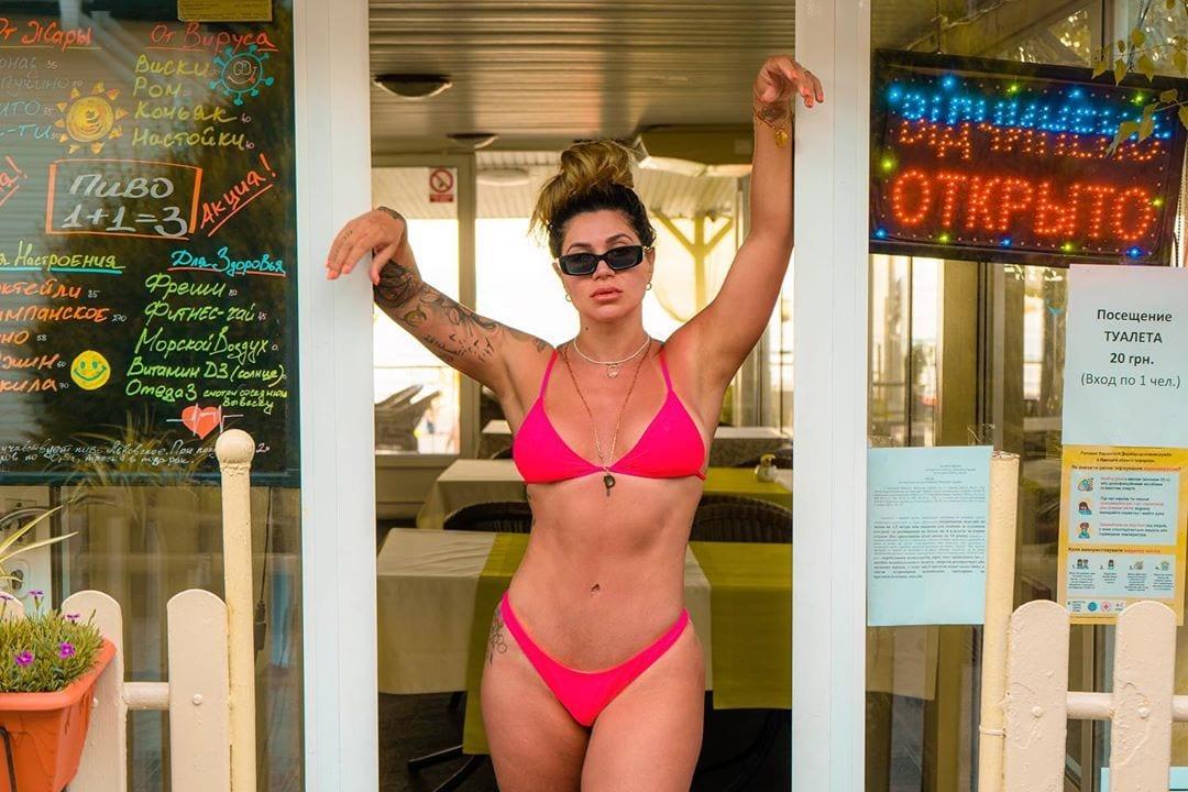 Dani Souza em foto na porta de restaurante.