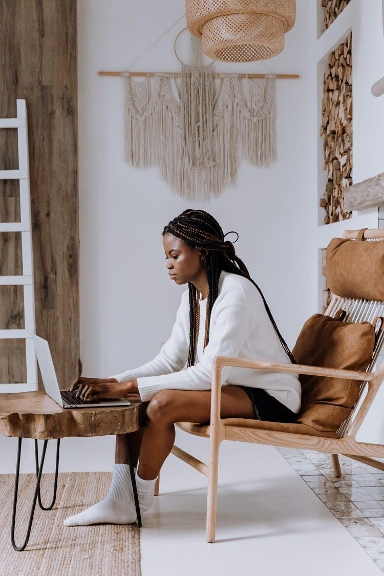 mulher sentada em poltrona fazendo aula online