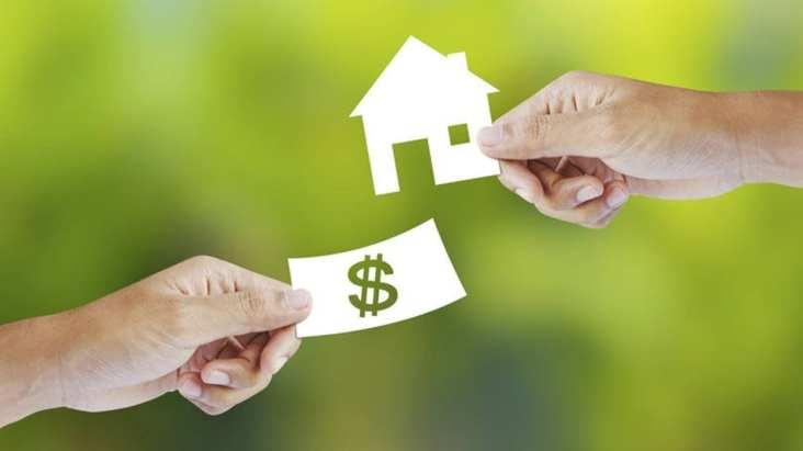 Imagem de mãos trocando dinheiro por casa.
