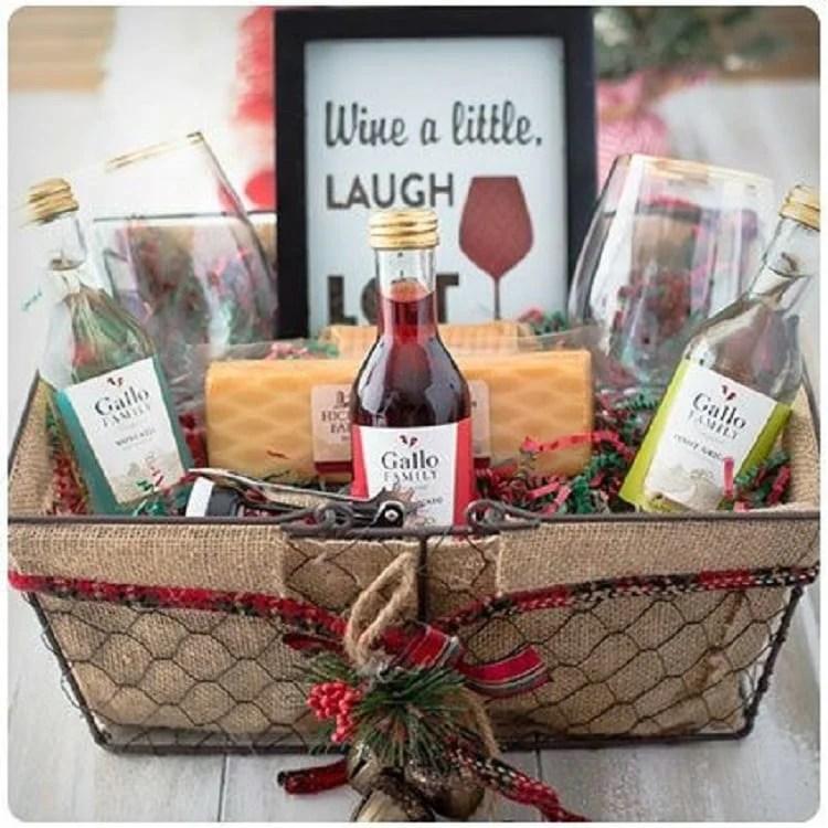 cesta de natal com garrafinhas de vinho, taças, saca-rolhas, queijos e um quadrinho