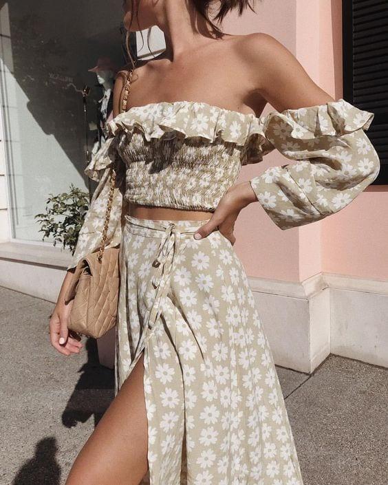 Menina usando conjunto de saia e blusa, com estampa floral.