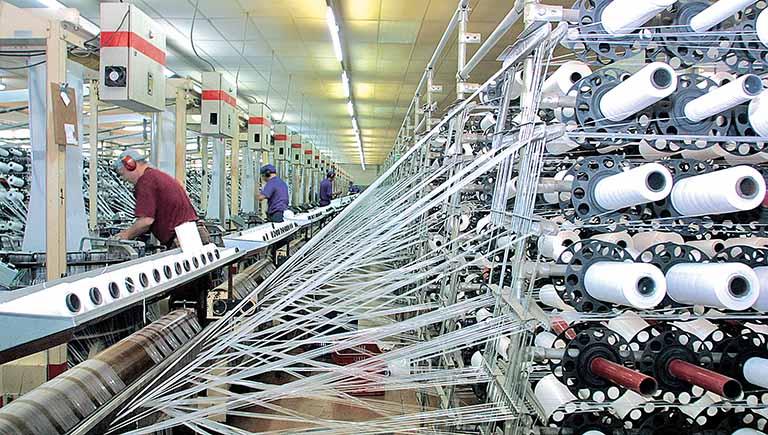 foto de tecelagem com vária tubos de linha - Crise na matéria-prima