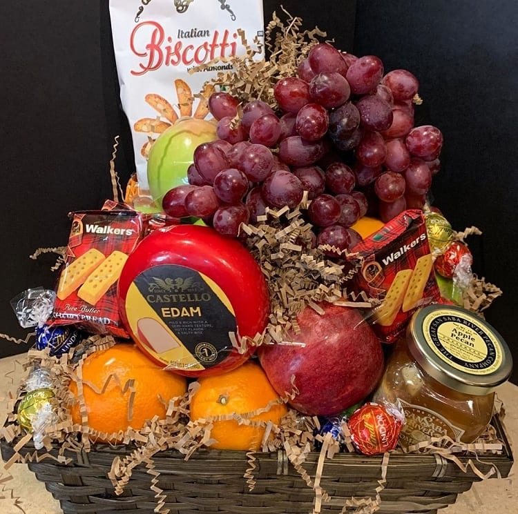 frutas frescas, queijos, biscoitos e geleias em um cesto de vime