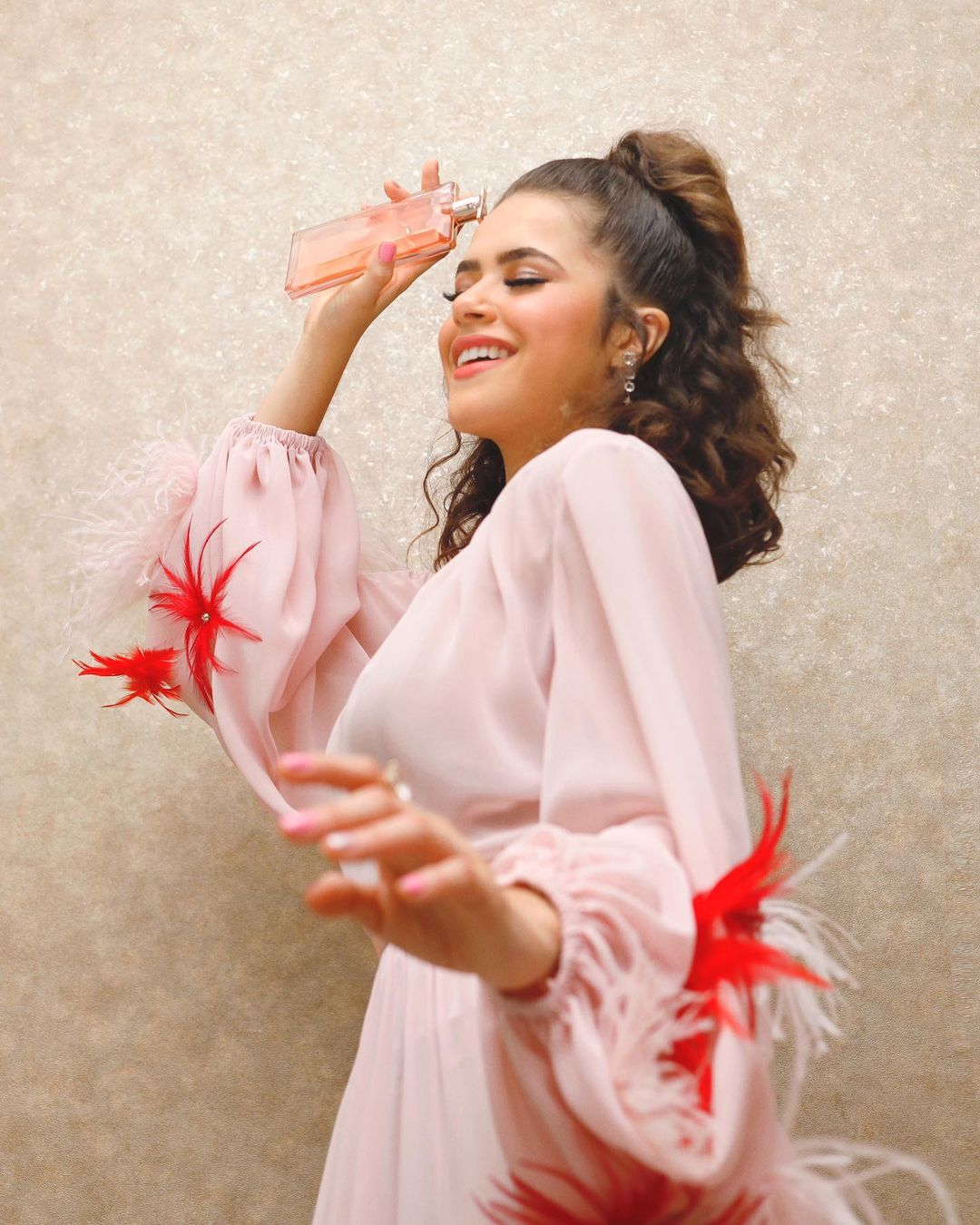 Foto da atriz segurando perfume Idôle da Lancôme.