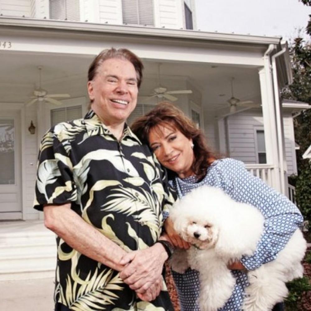 Famosos ricos, Silvio e esposa em frente a casa.