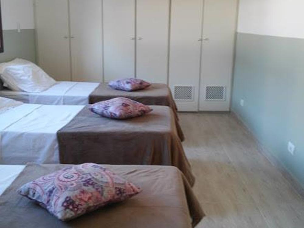 Foto de quarto com três camas.
