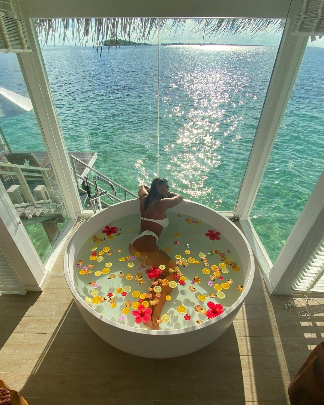 Atriz na banheira e vista incrível do seu quarto de hotel.