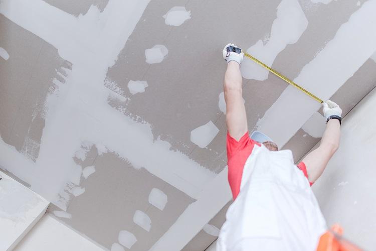 homem medindo forro de drywall