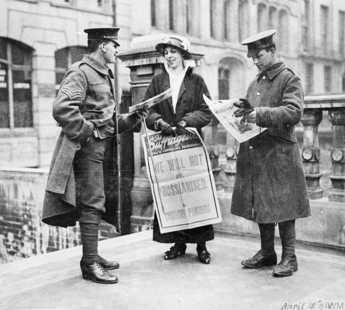 """Sufragista mostrando um jornal a dois oficiais britânicos e segurando um poster que diz """"Nós não vamos ser prussianizados"""". 1915."""
