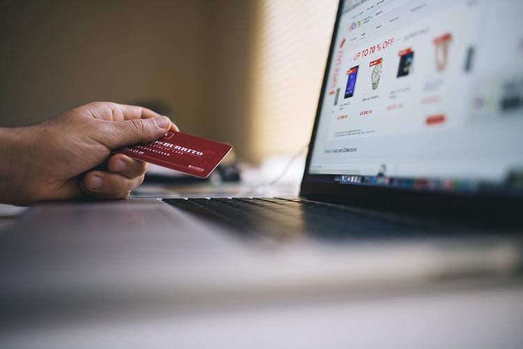 pessoa usando cartão de crédito em site de cupons de desconto