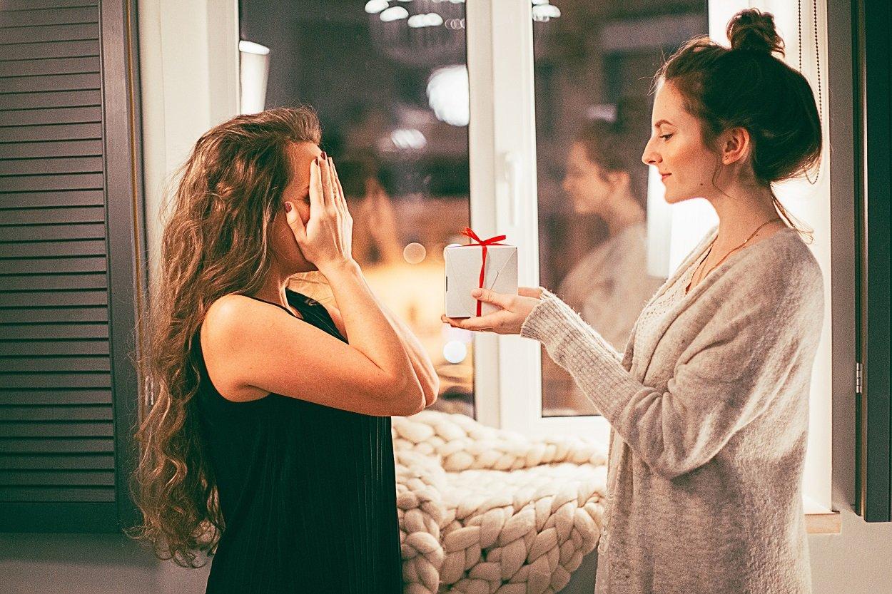 mulher fazendo surpresa para amiga com mini presentes